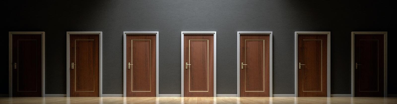 Sieben geschlossene Türen in einer dunklen Wand