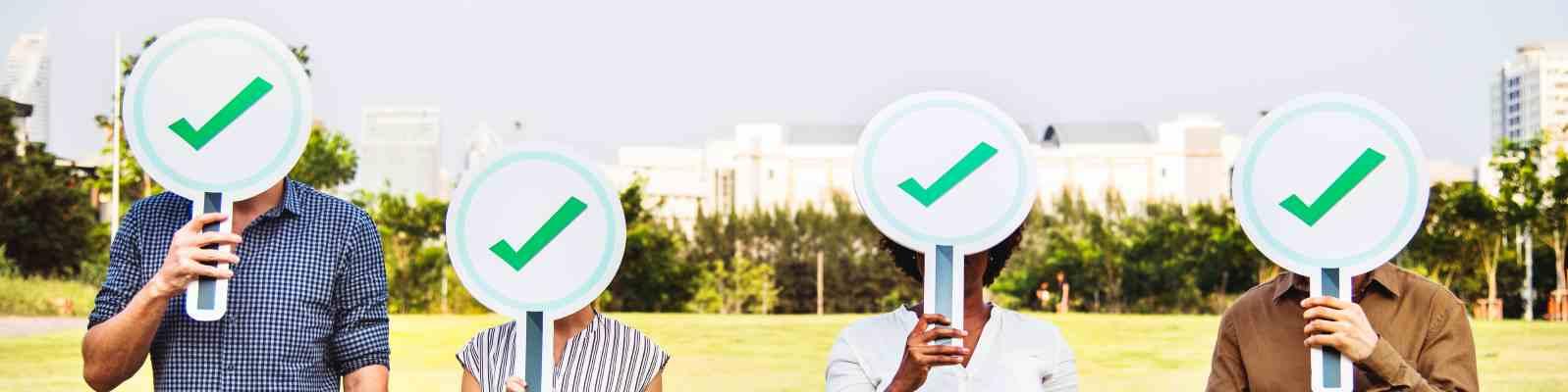 vier Personen tragen jeweils ein rundes Schild mit einem grünen Haken vor dem Kopf
